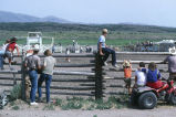 Rodeo spectators lined up against fence during 4th of July celebration (GCCS_CCE018_7)