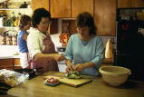 Kathleen Tanner instructing Amy Tanner on making salad while Angie works behind them...