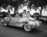 Class of 1962 students riding in a parade;