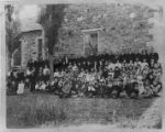 Group in front of old rock church, Mendon, undated