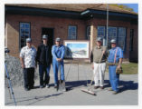 Group of men standing in front of a painting and new construction of Mendon station (2 of 3)