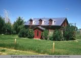 Log house with red trim and silver roof, Mountain View, Wyoming, 1967