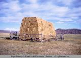 Pole fence panels around hay stack, Wyoming, 1964