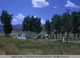 Pole fence surrounding frame house, Wyoming, 1967