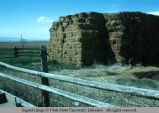 Pole fence protecting hay stack, Willard, Utah, 1977