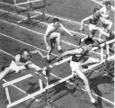 Men running hurdles in an intramural track and field event, 1950s