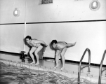 Two students poised to dive into the Smart Gymnasium pool, 1950s