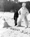 Man standing next to a snow sculpture of a logger with an ax and a chopped down tree at the Winter...