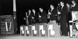 "Band playing on stage next to file cabinent labeled ""Jokes File,"" 1950s"