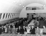 Group of men seated at banquet tables in a large room