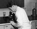 Man using microscope in a lab, 1930s