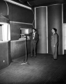 Two men standing in a room with a radio mic, late 1950s