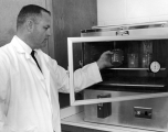 Man checking on a substance kept in a temperature controlled device