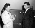 Man pointing out a substance in a vial to another man, 1950s