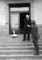 Utah Agricultural College President E. G. Peterson shaking hands with a man on the steps of a...