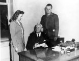 USAC President Franklin S. Harris seated at his desk with a young man and woman on either side of...