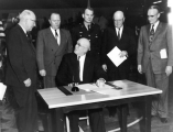 Governor George Dewey Clyde signing the legislative act changing the name of Utah State...