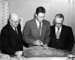 Three men going over architectural sketchs and floor plans, 1960s
