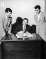 USAC President Louis L. Madsen looking at a yearbook with two other men, 1950s