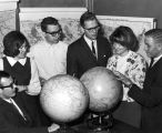 Students gathered around two globes, 1960s