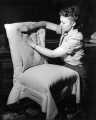 Woman reupholstering a chair, 1940s