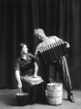 Woman stirring a pot and a man with an accordian on stage, 1917