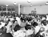 Large group of people eating at a banquet, 1950s