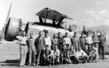 Men posing with a small airplane, 1940s