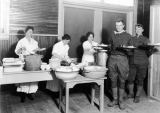 Three women and two men serving food, circa 1910