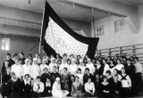 Group of women posing in front of a flag, circa 1919