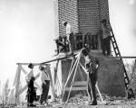 Five men examining the smokestack while the supporting bricks at its base were being torn out,...
