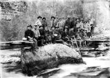 People sitting on a log bridge, circa 1920