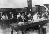 Students looking through microscopes in a science class, early 1900's