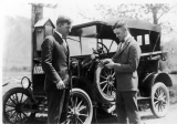 Two men with a rope standing in front of a car, 1920s