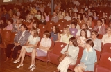 Men and women with name tags seated in chairs in an auditorium, 1970s