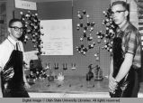 Students next to a molecule display, 1950s