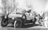 People riding in a decorated automobile, March 20, 1915