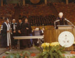 University President Glen L. Taggart speaking a podium with William Loos, Jane Tibbals, J.D....