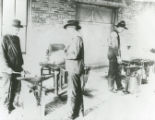 Three men working at two forges in a blacksmith shop
