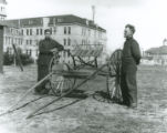 Two men posing next to a wagon outdoors