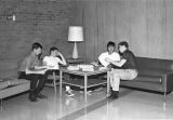 Four male students studying at a table in a student lounge
