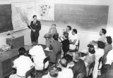 Professor teaching a group of students in classroom, 1960s