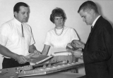 One man demonstrating the use of a laminating press while two other people observe, 1960s