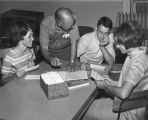 Students and a professor gathered around a table, 1960s