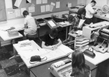 Students writing and typing in media center, 1960s