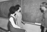 Three students solving a math equation at the blackboard, 1960s