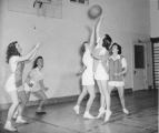Women playing basketball in a physical education class, 1940s