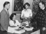 Student staff looking at The Scribble magazine, early 1950s
