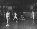 People playing badminton in men's gym in Smart Gymnasium, 1950s