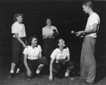 Man coaching four women in softball, 1940s